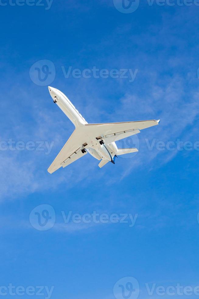 Flugzeug fliegt über Kopf mit blauem Himmel foto