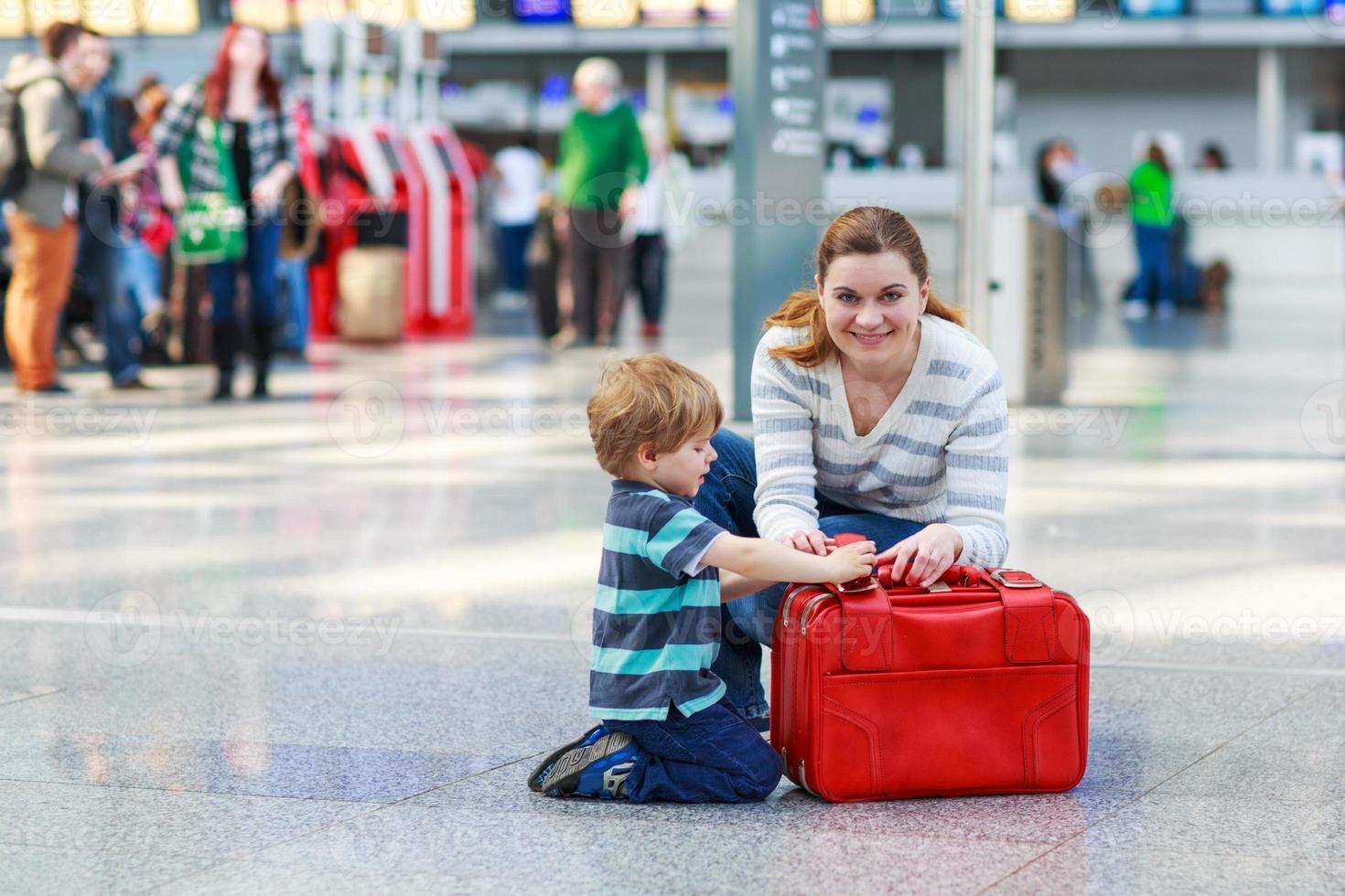 Mutter und kleiner Junge am Flughafen, drinnen foto