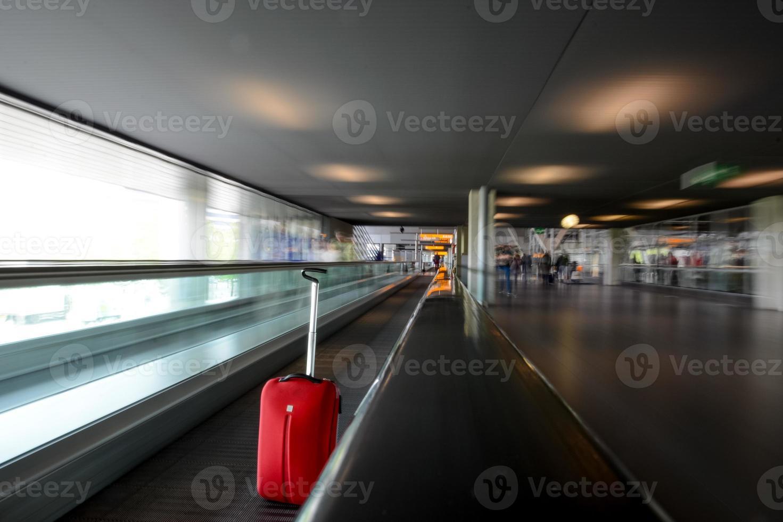 unscharfe Rolltreppe mit rotem Wagen im Flughafen foto