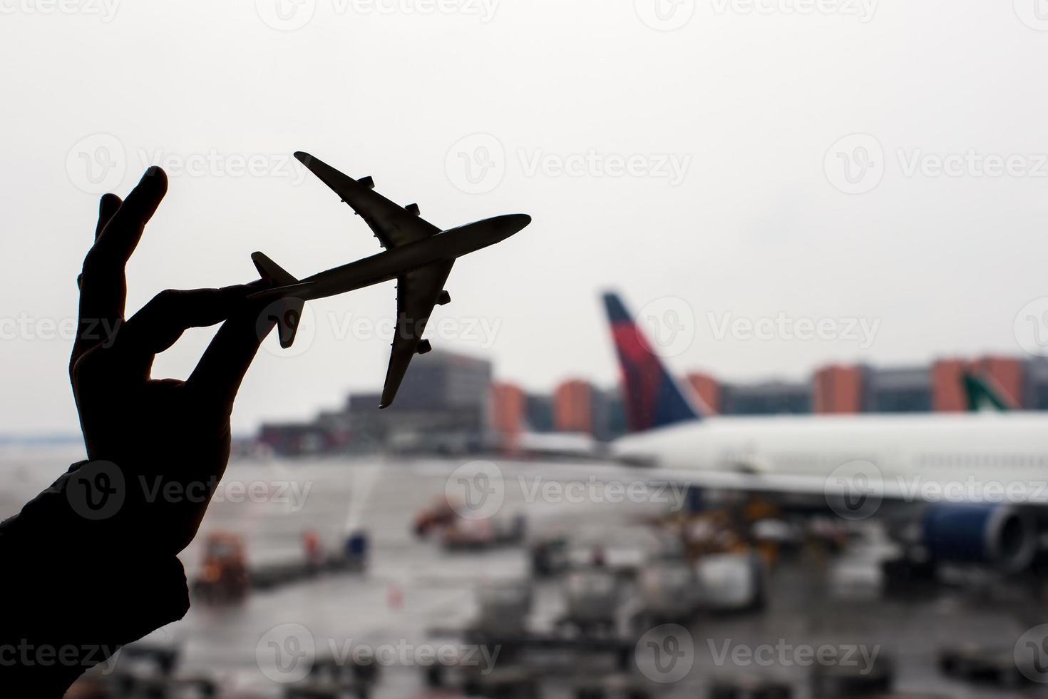 Schattenbild eines kleinen Flugzeugmodells auf Flughafenhintergrund foto