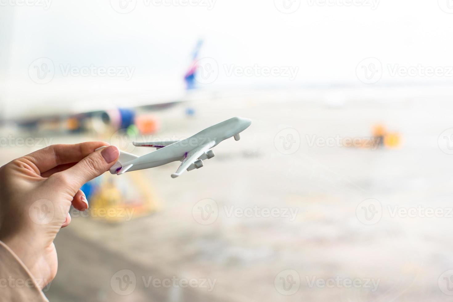 Nahaufnahmehand, die ein Flugzeugmodell am Flughafen hält foto