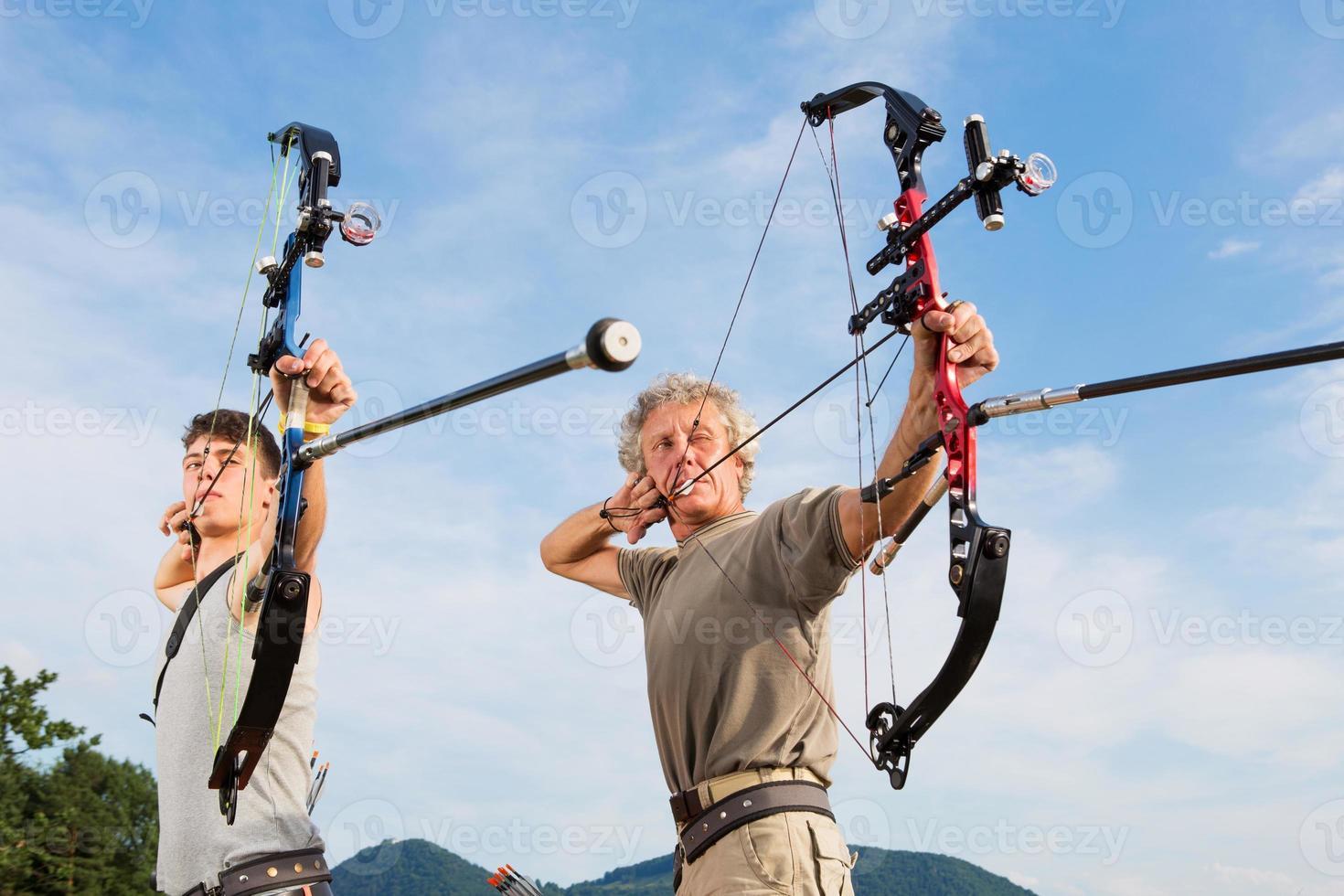 Bogenschützen ... Vater und Sohn üben das Schießen von Zielen foto