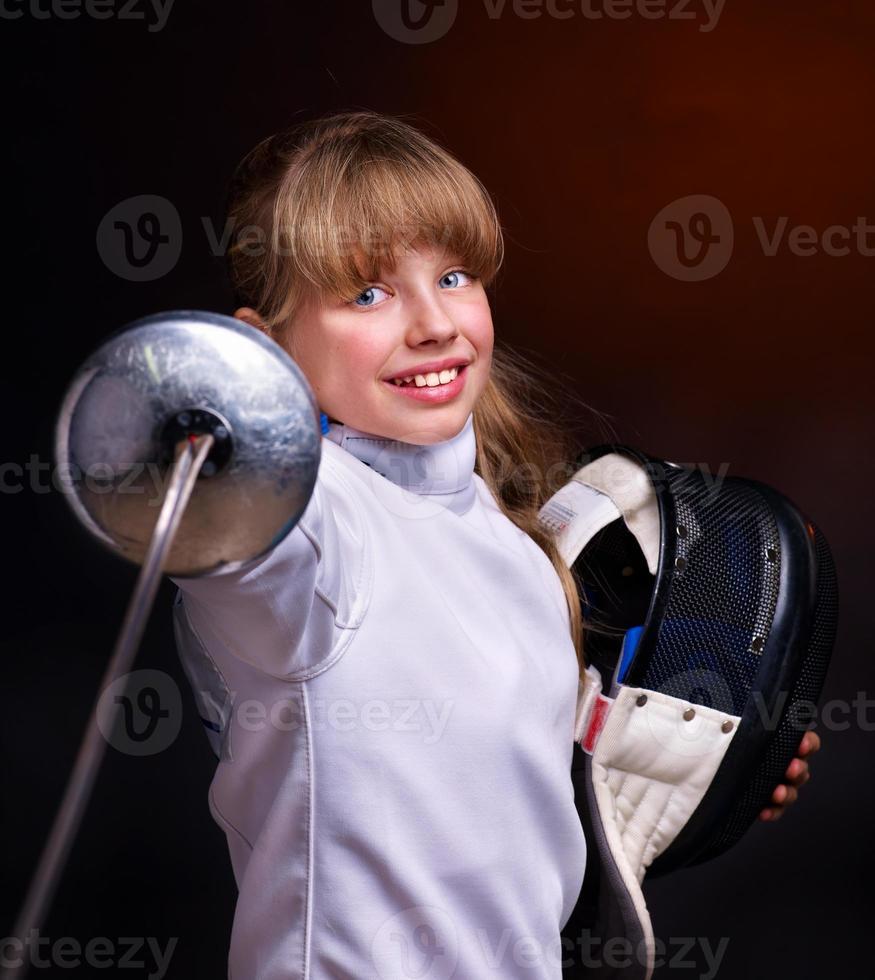 lächelndes Mädchen im Fechten tragen weisenden Degen auf Kamera foto