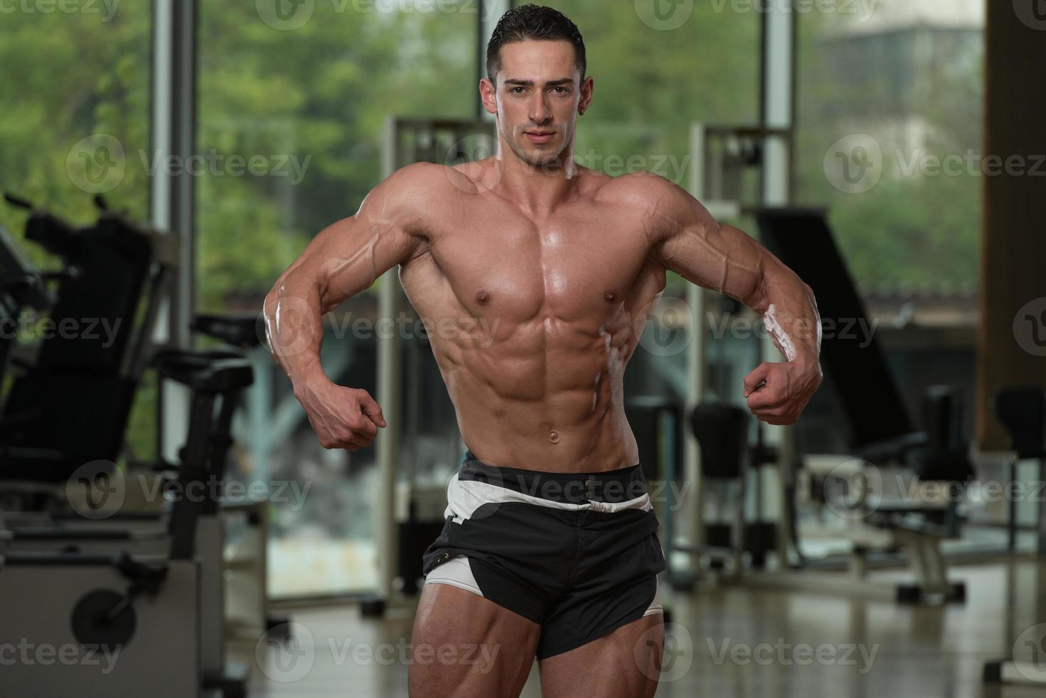 ernsthafter Bodybuilder, der im Fitnessstudio steht foto