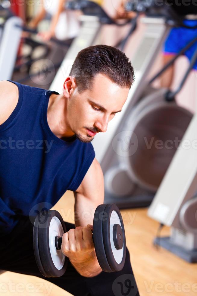 Mann, der im Fitnessstudio trainiert und Gewichte hebt foto