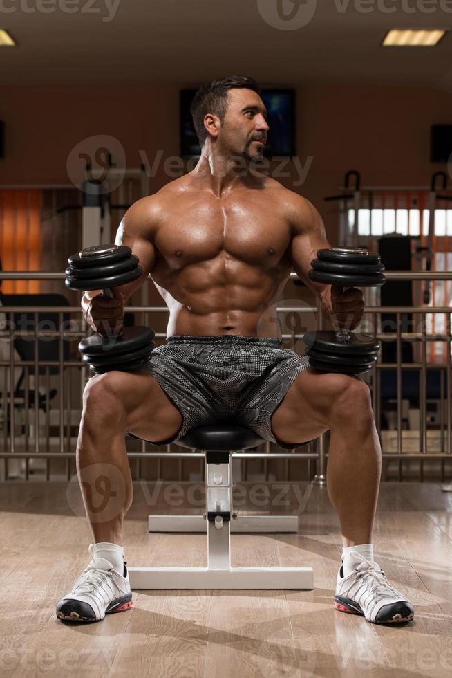 Bodybuilder, der schweres Gewicht für Schultern trainiert foto