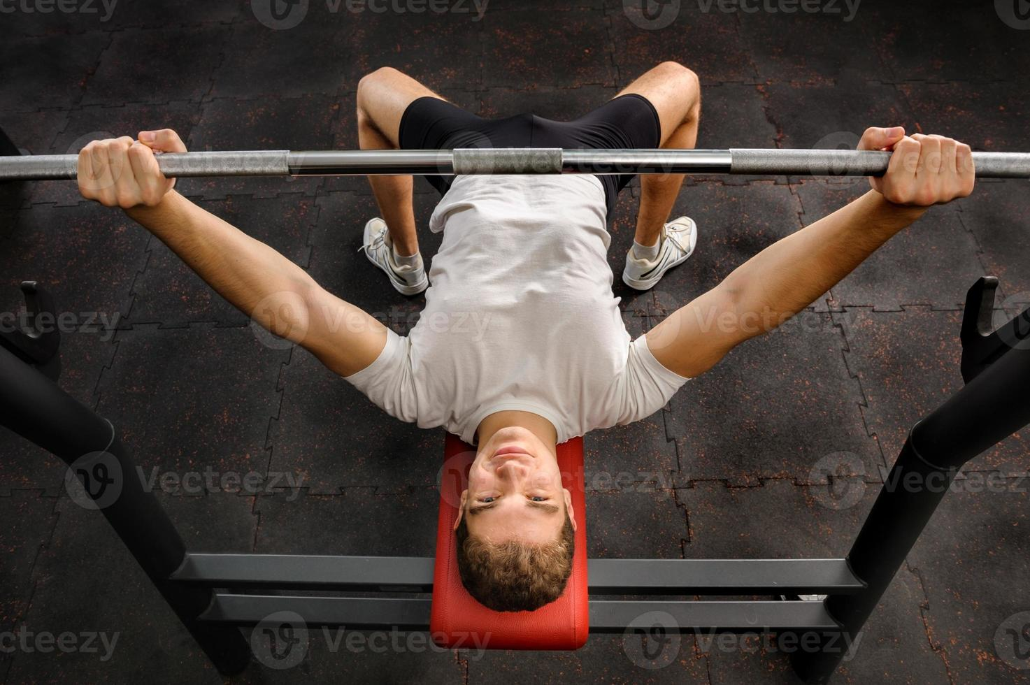 junger Mann, der Bankdrücken-Training im Fitnessstudio macht foto