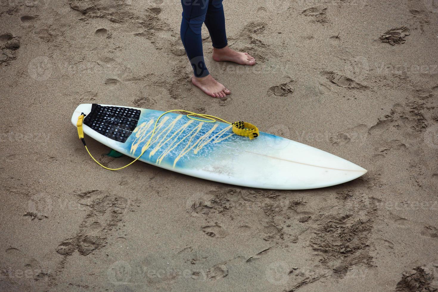Surfbrett am Strand neben den Surferbeinen. foto