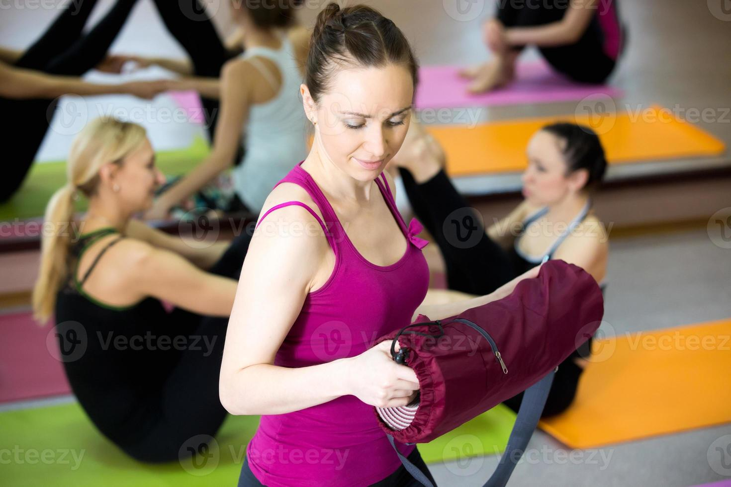 lächelndes Yogi-Mädchen, das Yogamatte im Fitnessstudio entfaltet foto