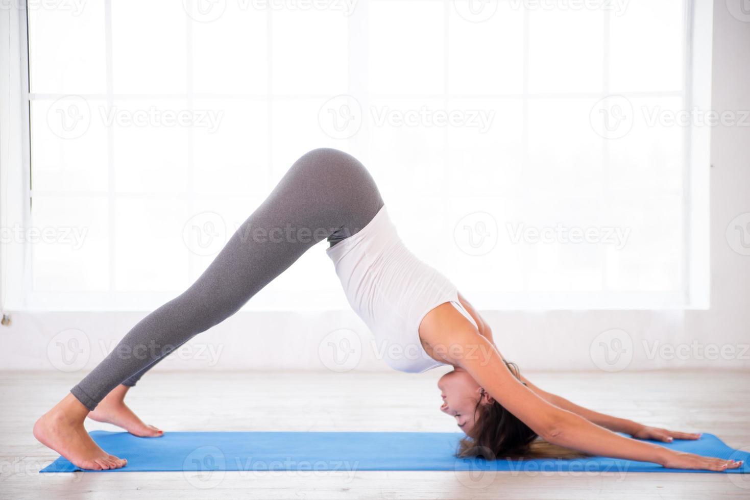 Yoga-Frau, die unten Hundehaltung tut foto