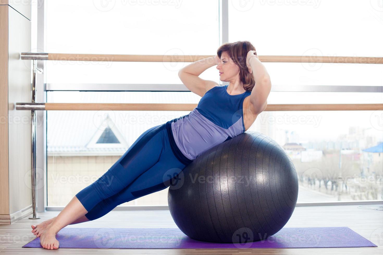 junges Mädchen, das im Fitnessstudio mit einem Ball trainiert foto