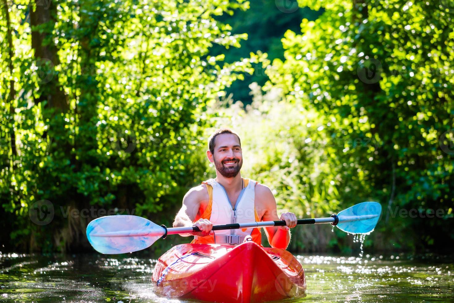 Mann, der mit Kajak auf Fluss für Wassersport paddelt foto