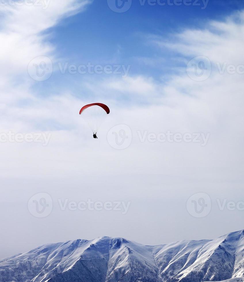 Gleitschirmschattenbild der Berge im windigen Himmel am Sonnentag foto