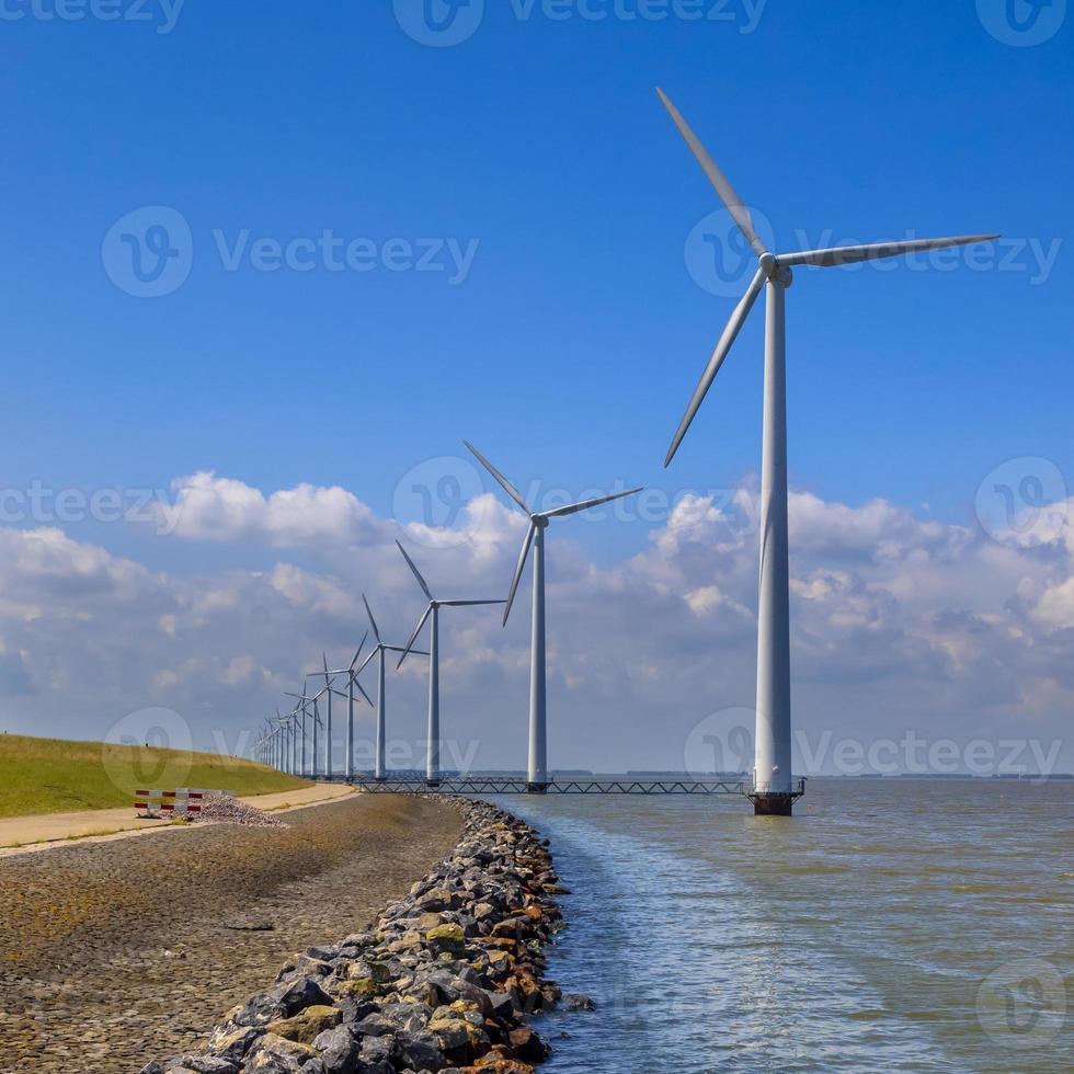 Reihe von Windkraftanlagen entlang eines Wellenbrechers foto
