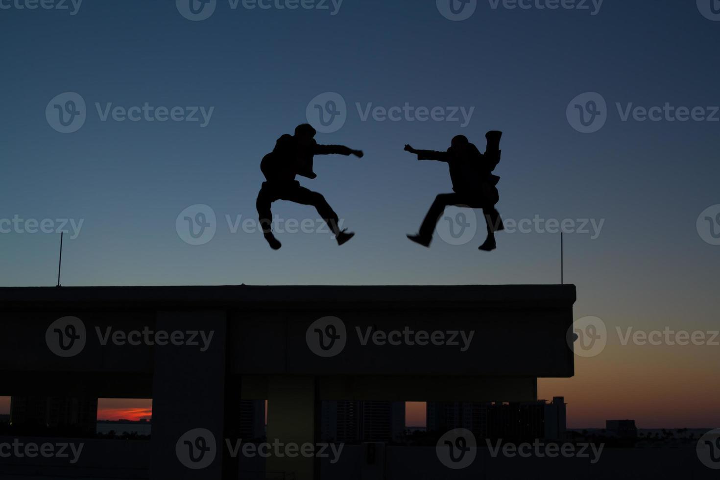 Zwei Männer machen Kampfkunst auf dem Dach foto