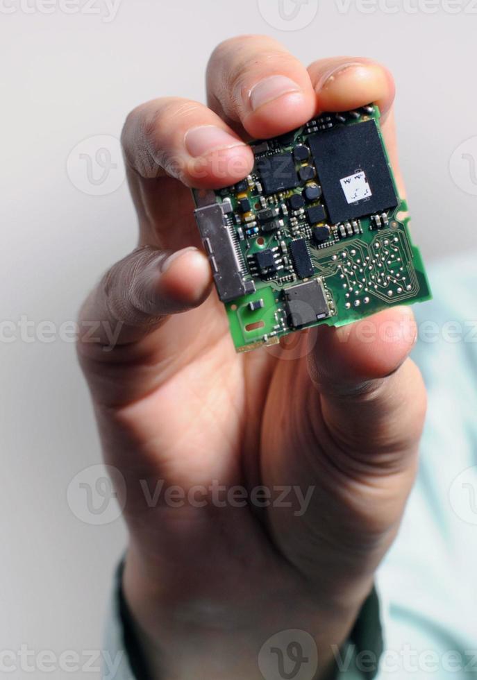 Hand hält Datachip an den Fingerspitzen foto