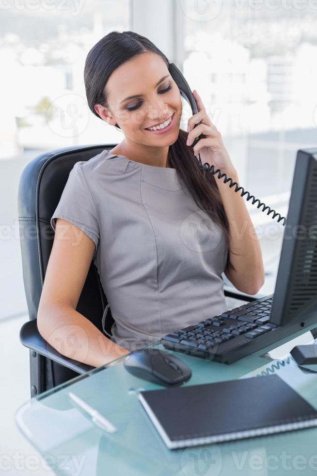lächelnde attraktive Geschäftsfrau, die Telefon beantwortet foto