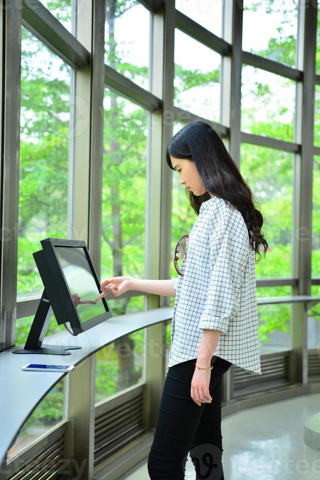 Mädchen stand auf, um Computermonitor zu benutzen foto