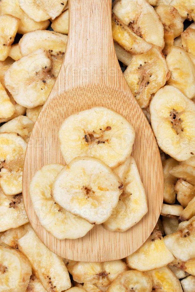 Nahaufnahme von getrockneten Bananenchips auf einem Holzlöffel foto