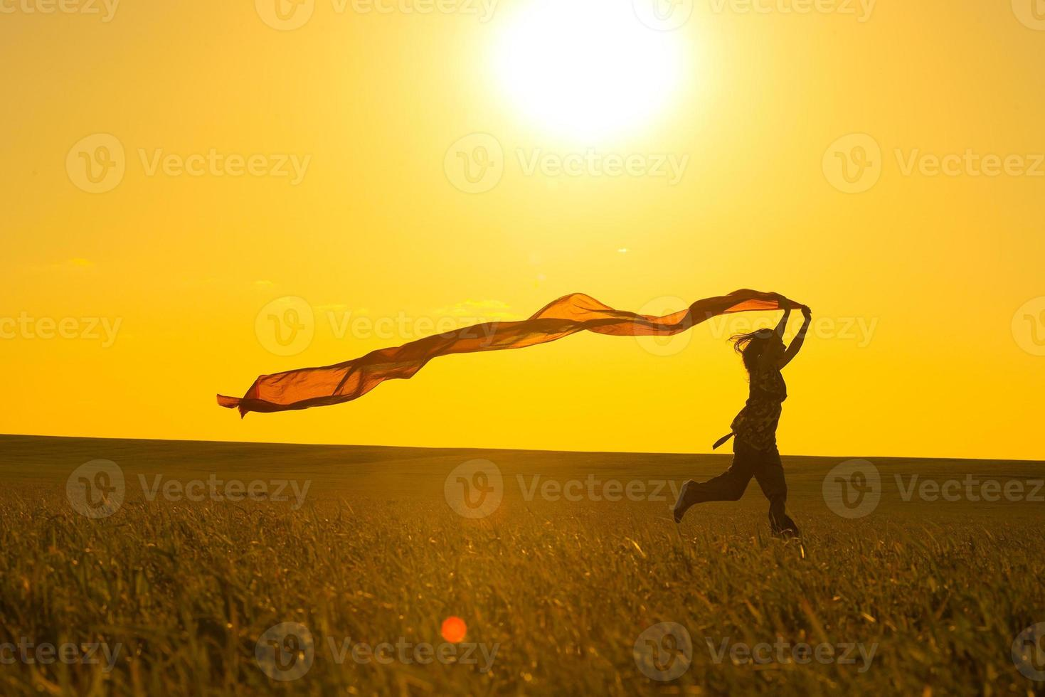 junge Frau läuft auf einer Landstraße bei Sonnenuntergang in foto