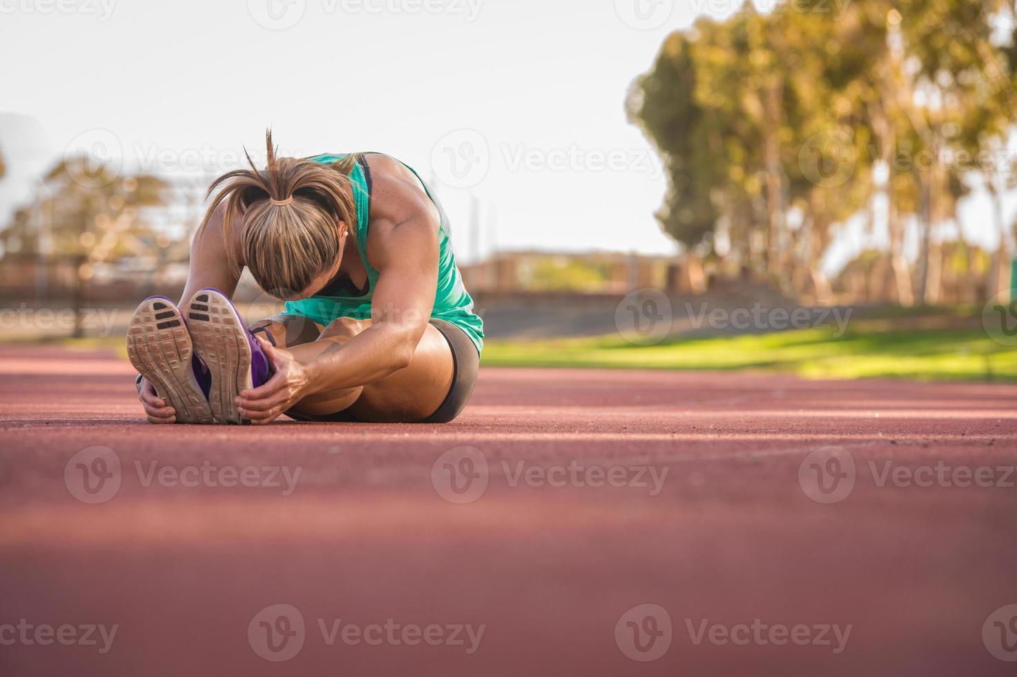 Sportlerin, die sich auf einer Laufbahn ausdehnt foto