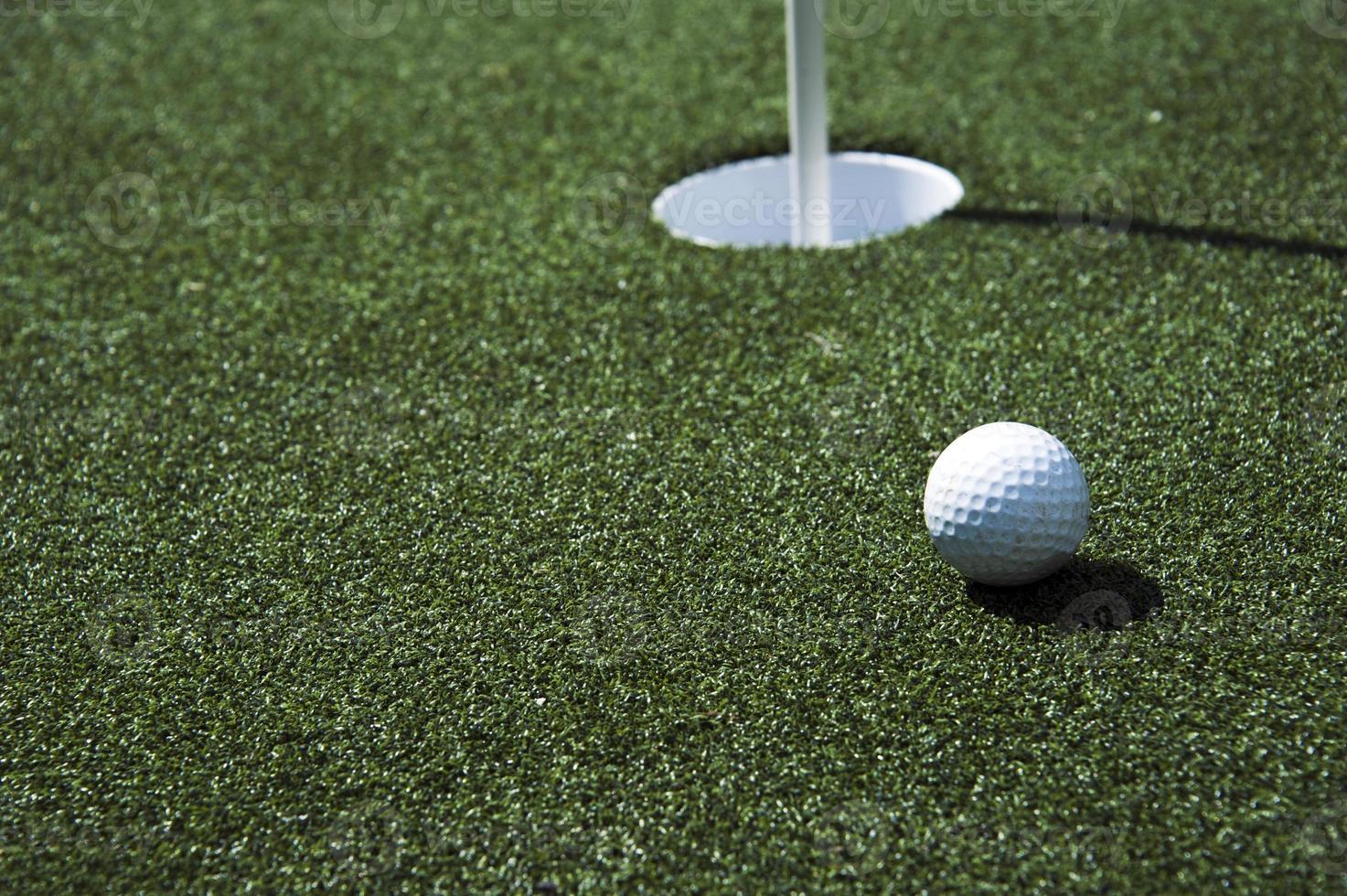 Golfball und Loch auf einem Feld foto