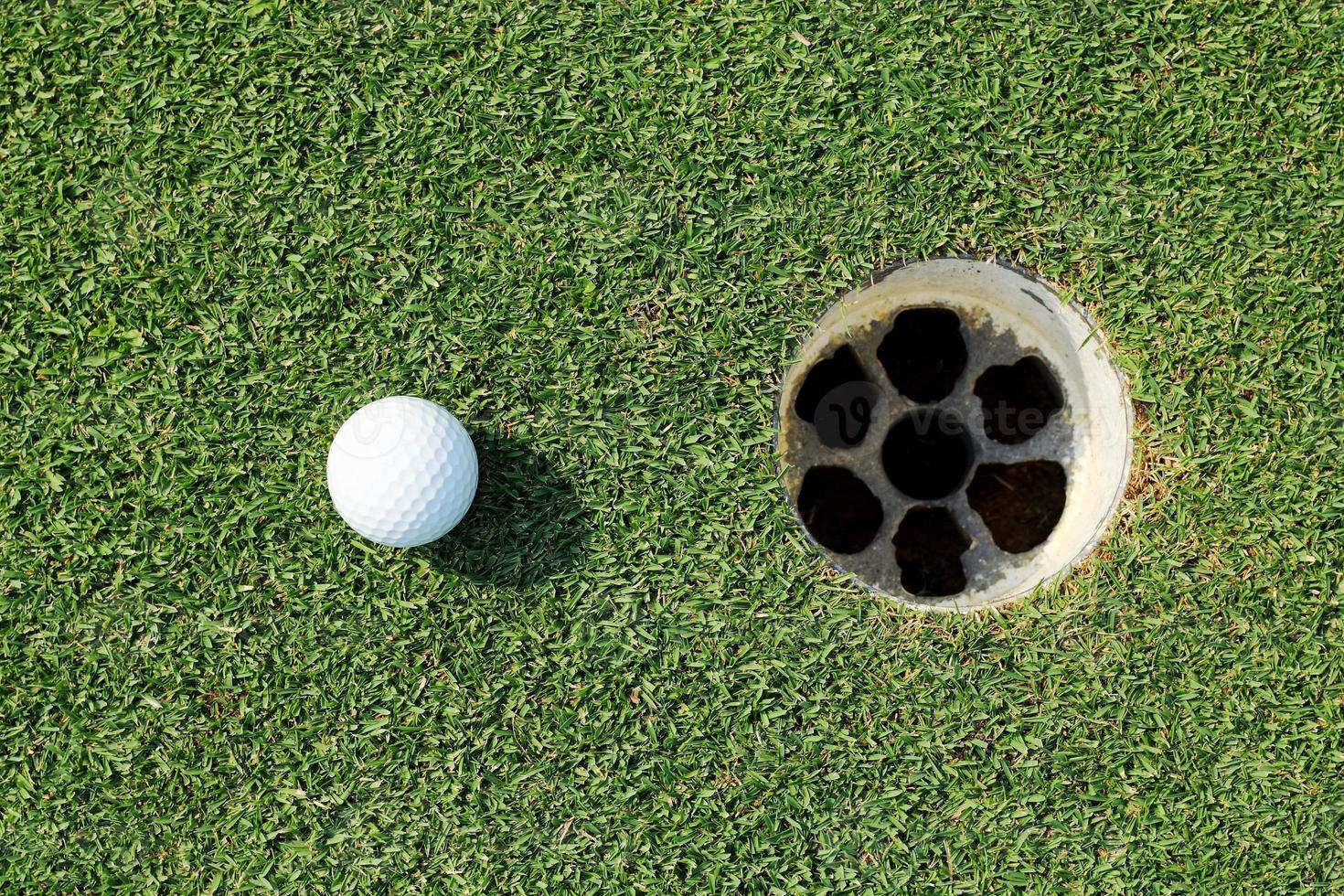 Golfball in der Nähe des Lochs foto