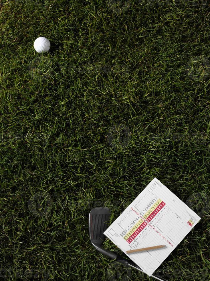 Golfball und Eisen auf grünem Gras foto