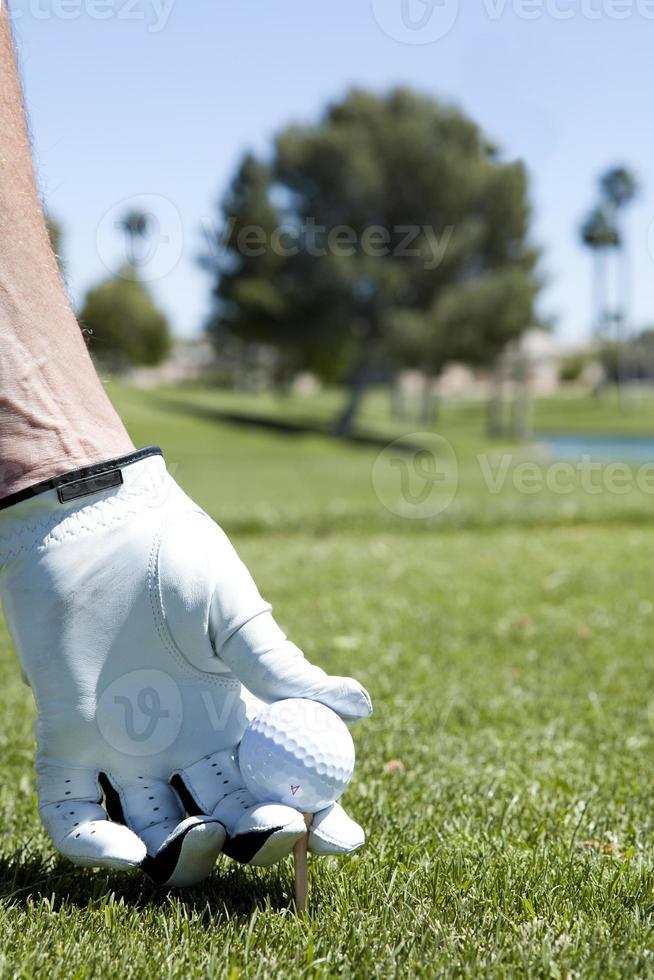 einen Golfball auf dem Abschlag abschlagen foto