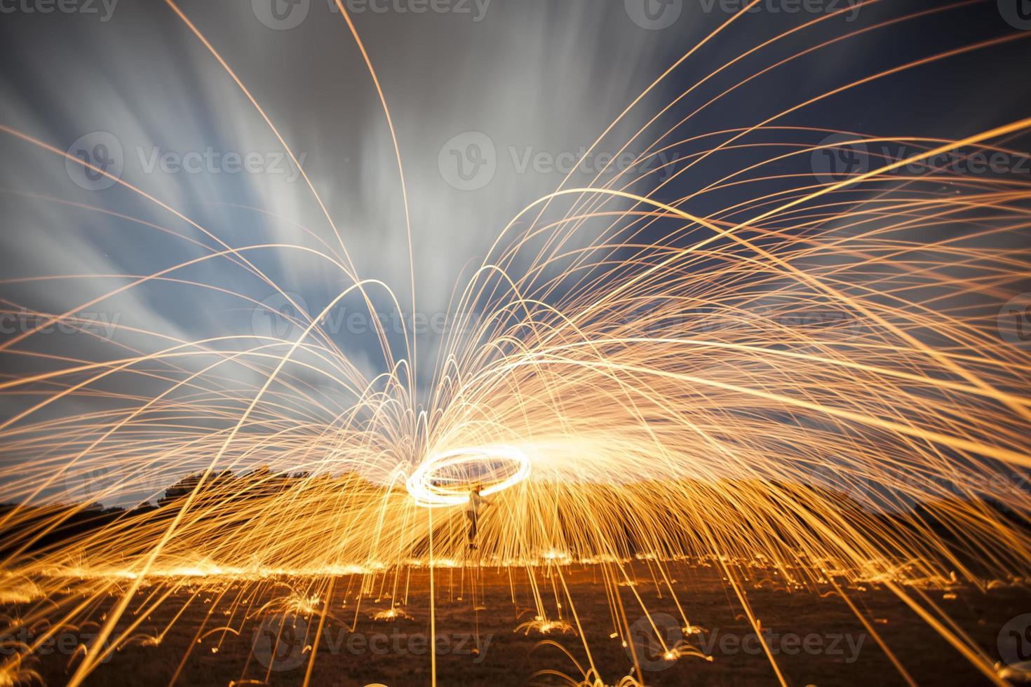 Schauer heiß glühender Funken aus sich drehender Stahlwolle. foto