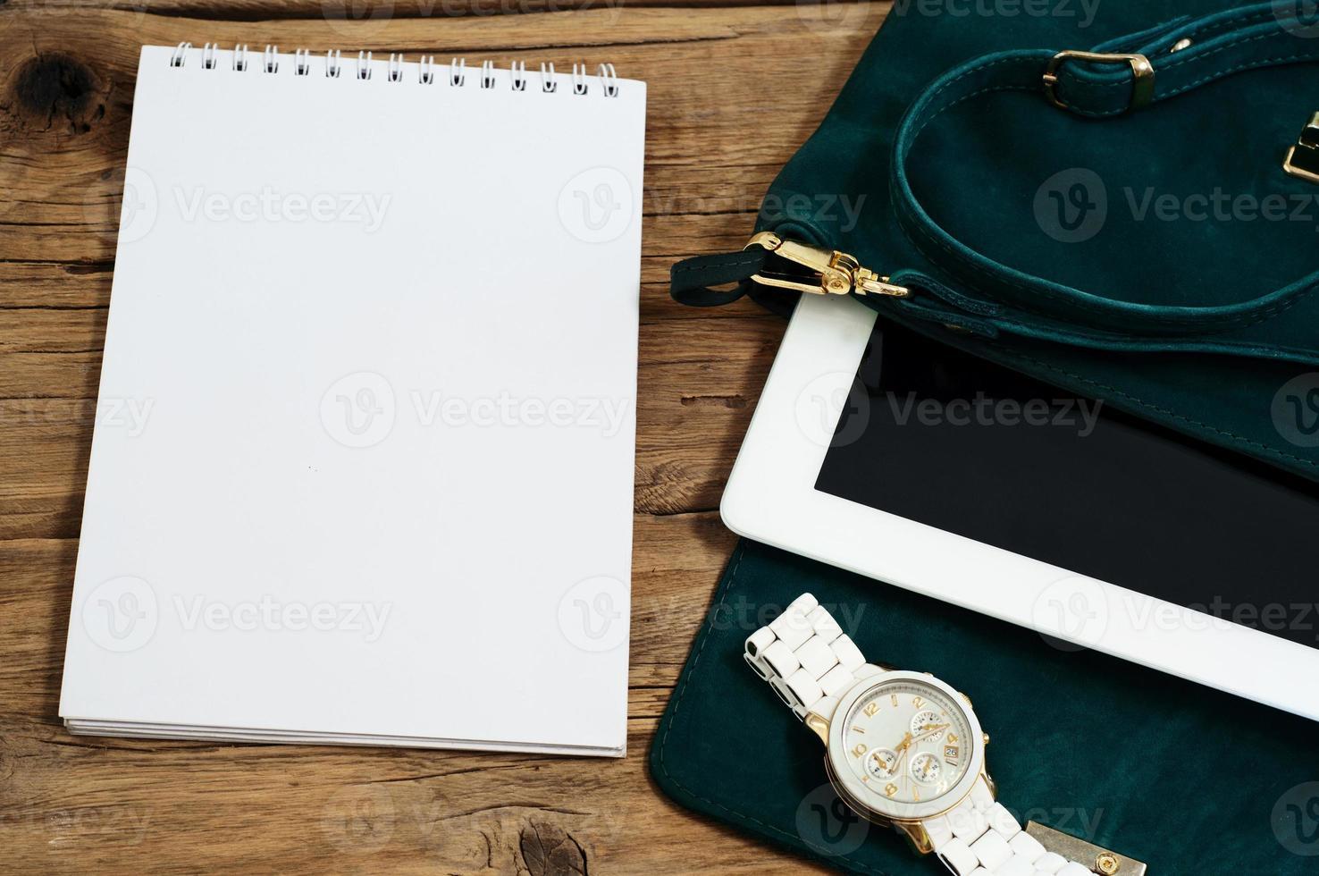 Notizbuch mit weiblicher Tasche, Tablet und Uhren foto