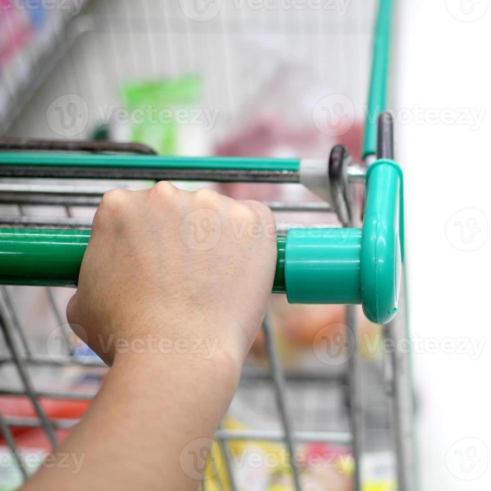 Hand auf Einkaufswagen foto