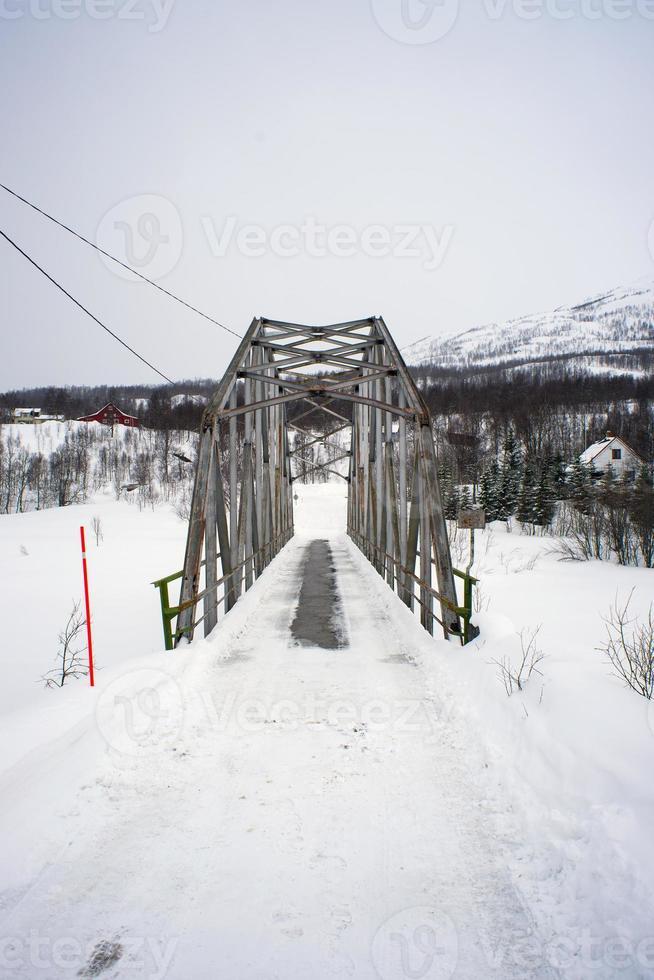 Brücke auf einem zugefrorenen Fluss in Nordnorwegen foto