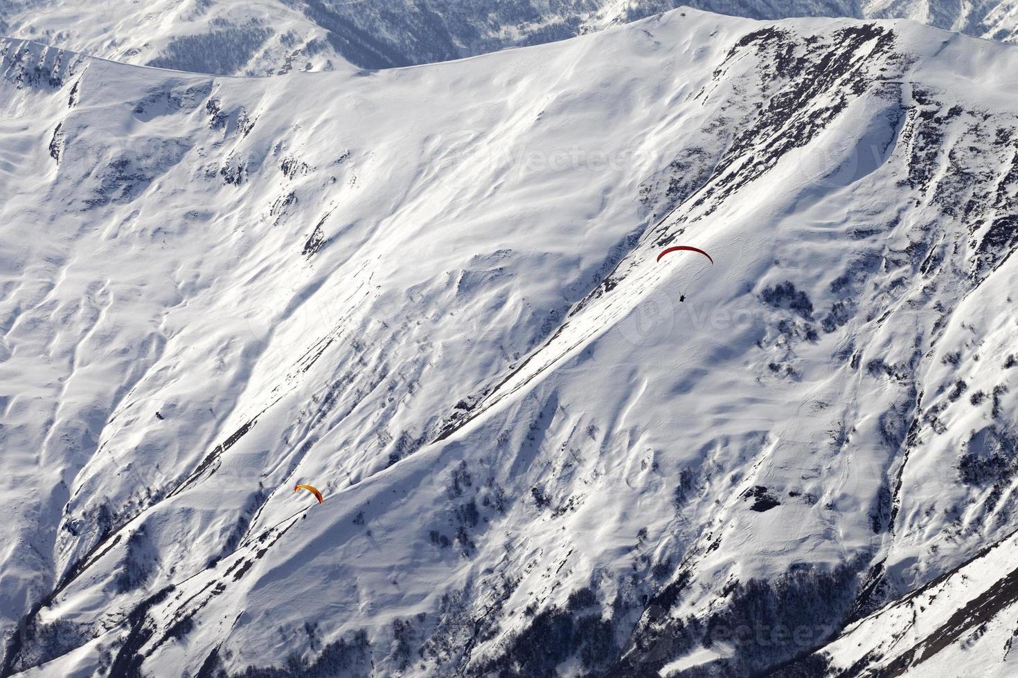 Gleitschirme von schneebedeckten Bergen foto