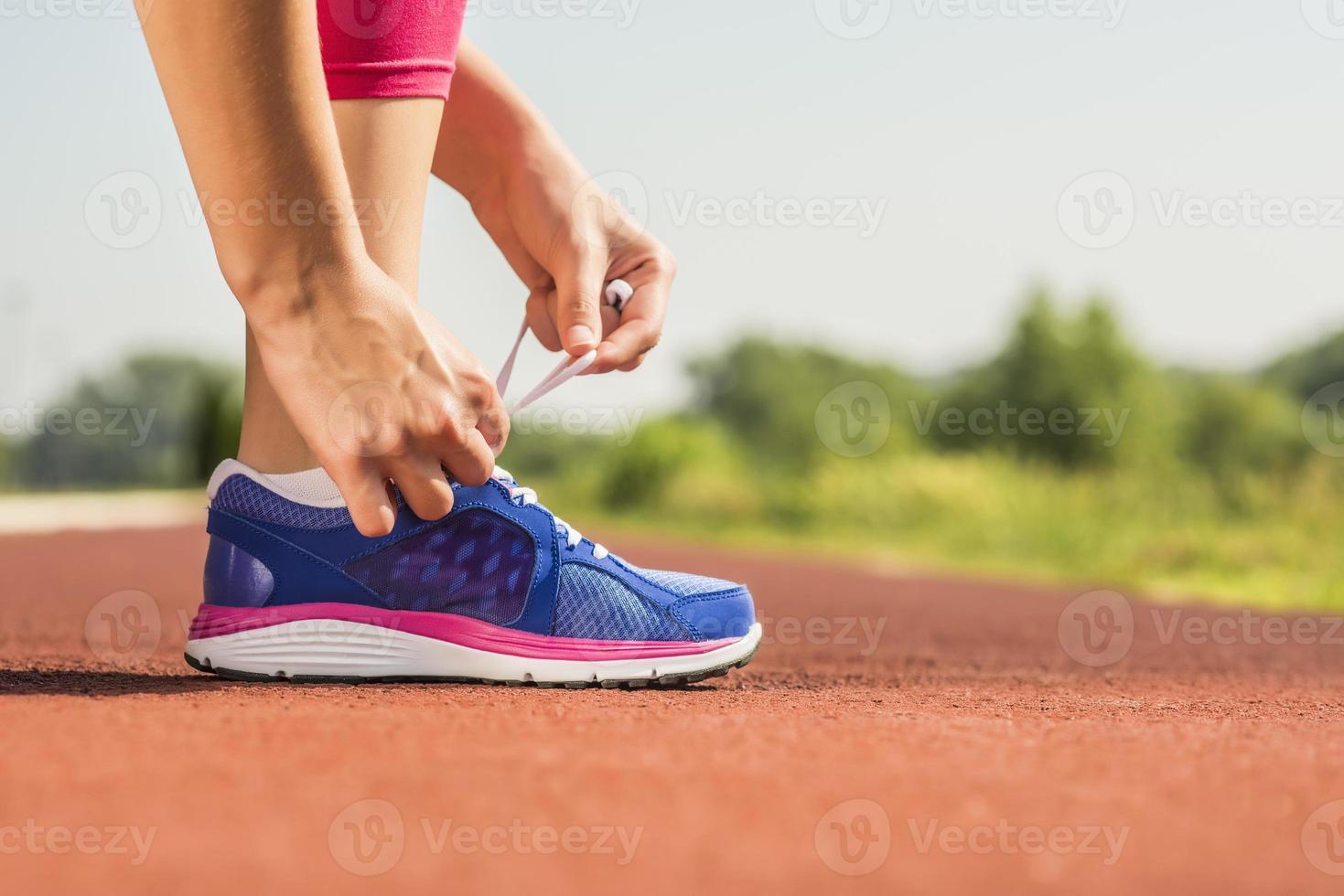 Nahaufnahme einer Frau, die die Schnürsenkel ihrer Laufschuhe festbindet foto