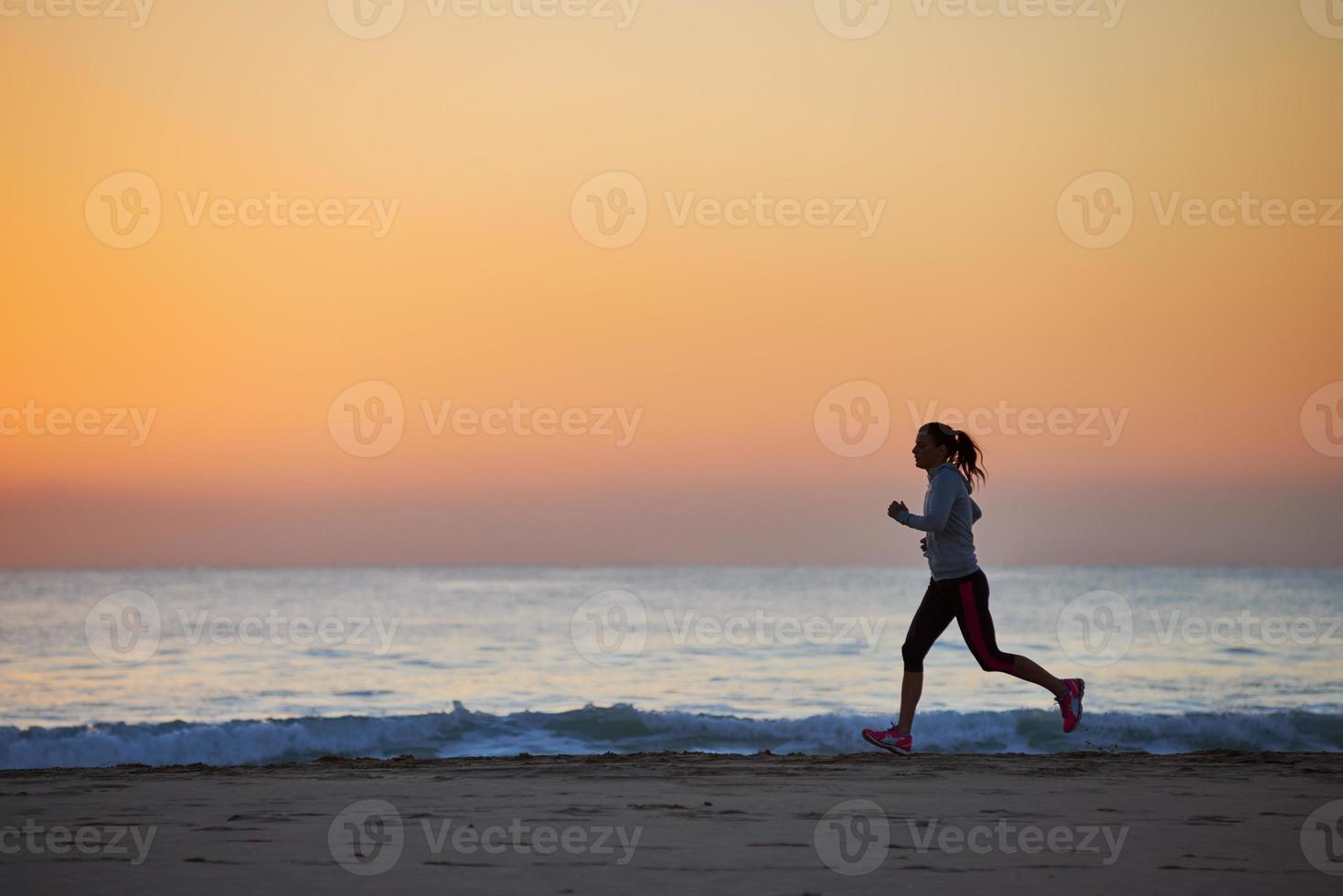 Fitnessfrau läuft am Strand foto