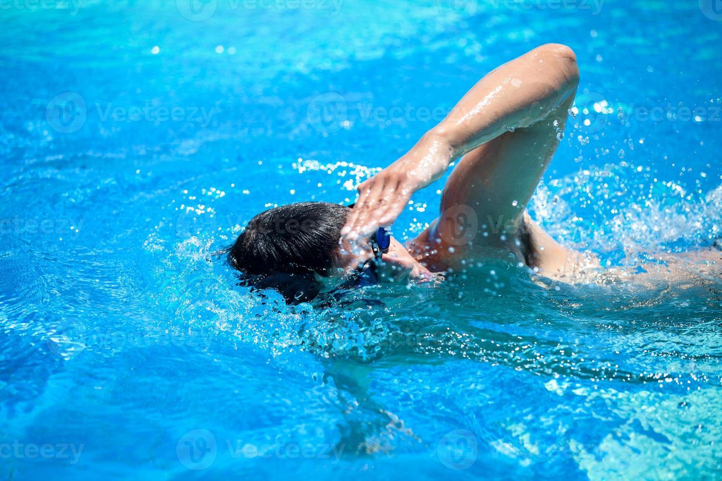 junger Mann, der in einem Pool schwimmt foto