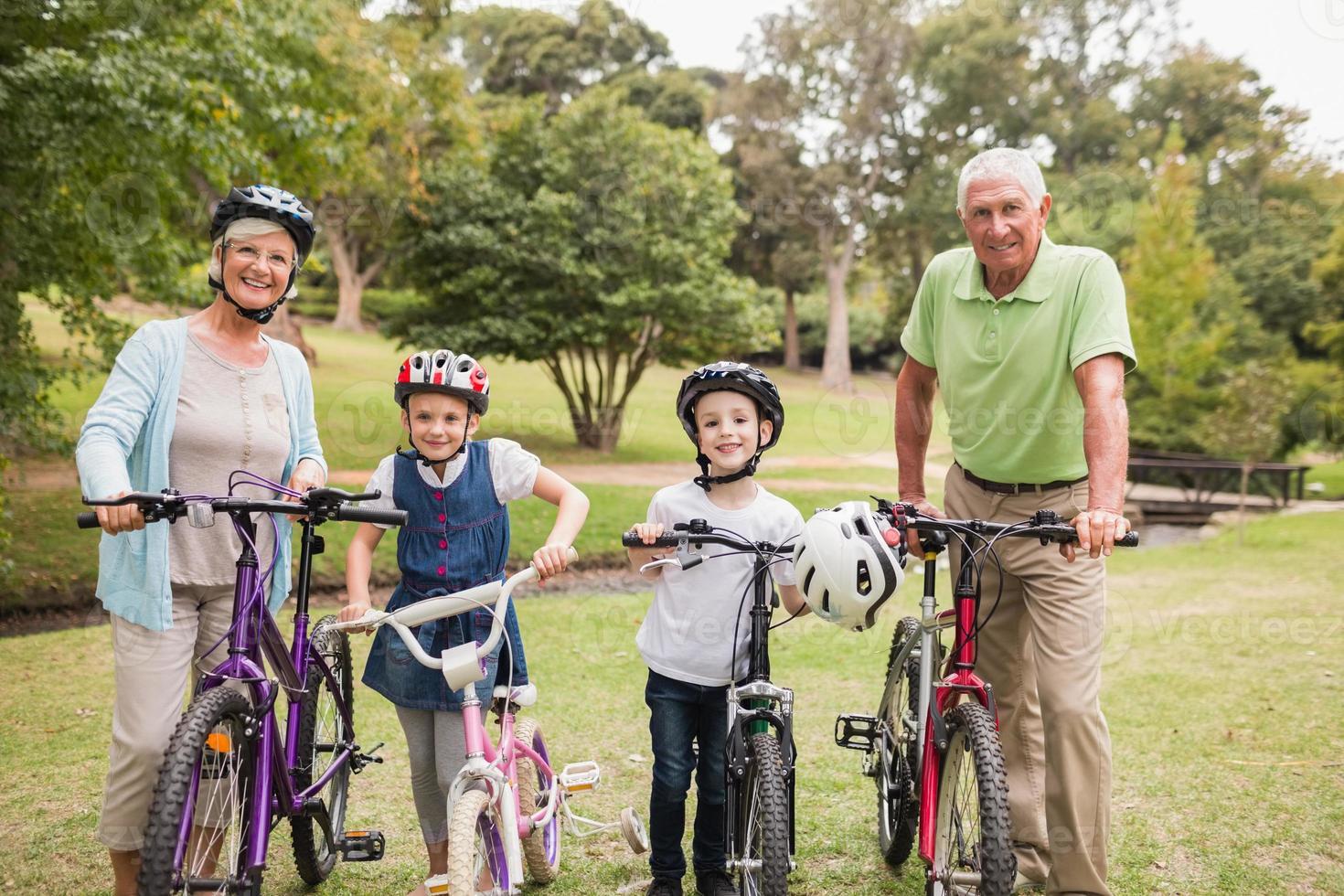 glückliche Großeltern mit ihren Enkelkindern auf Fahrrädern foto