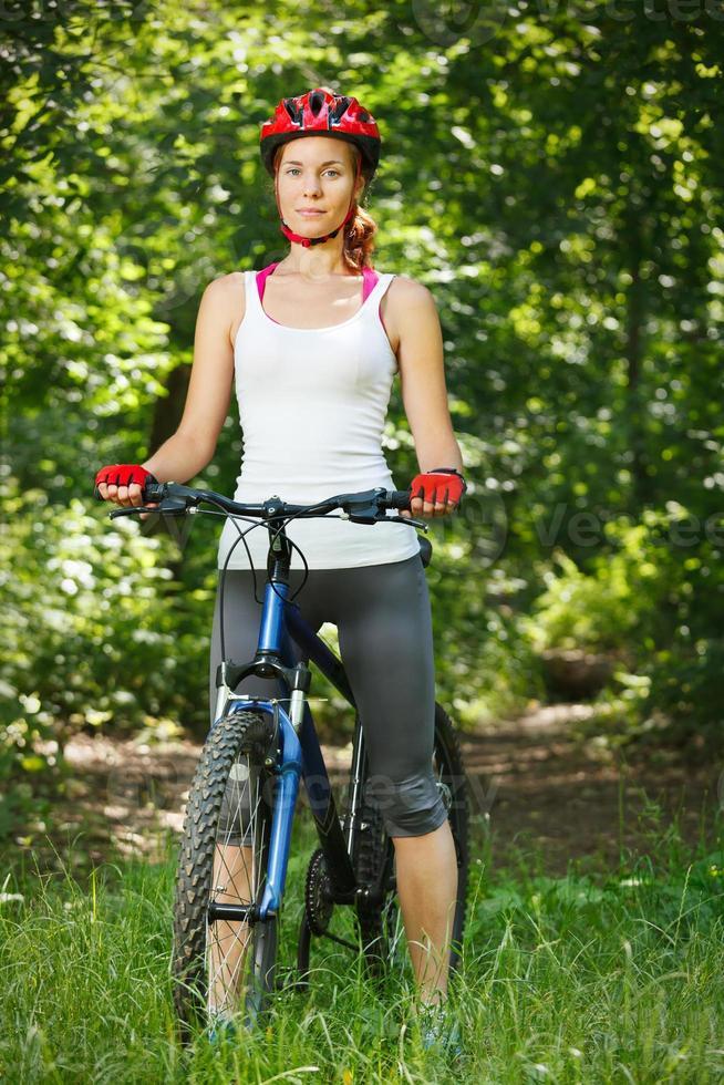 glückliche junge Frau beugte sich über den Lenker ihres Fahrrads. foto