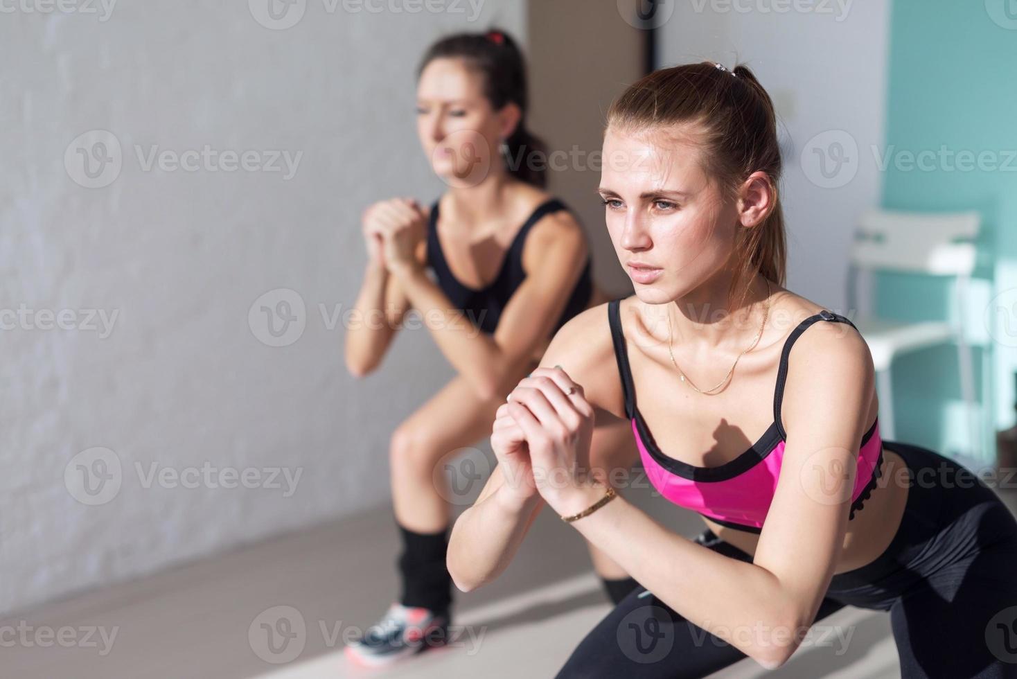 zwei Mädchen, die zusammen drinnen Kniebeugen machen und sich aufwärmen foto