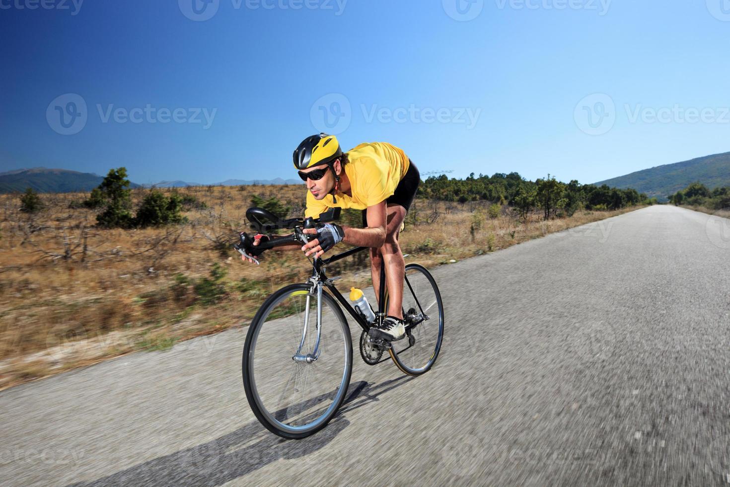junger Radfahrer, der Fahrrad auf offener Straße fährt foto