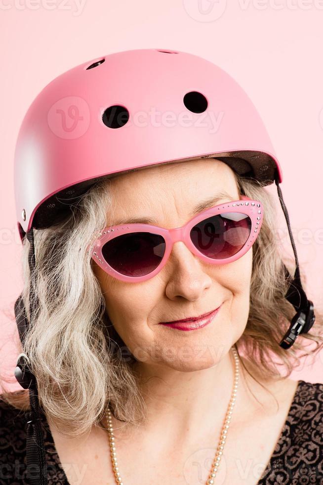 lustige Frau, die Fahrradhelmporträt rosa Hintergrund real trägt foto
