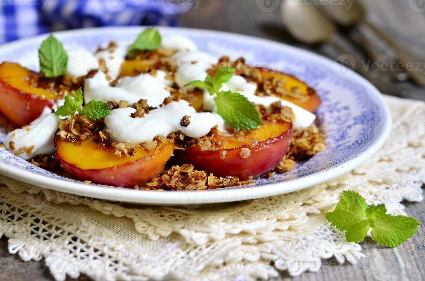 Gegrillte Pfirsiche mit Müsli und Schlagsahne. foto