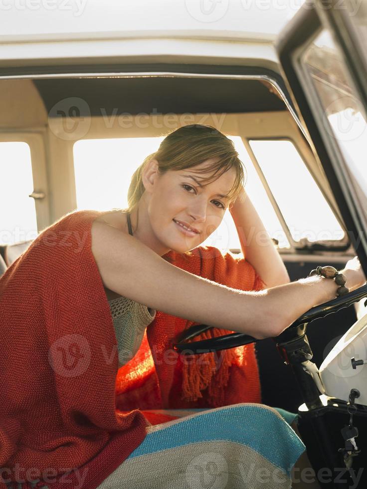 Frau sitzt am Fahrersitz des Wohnmobils foto