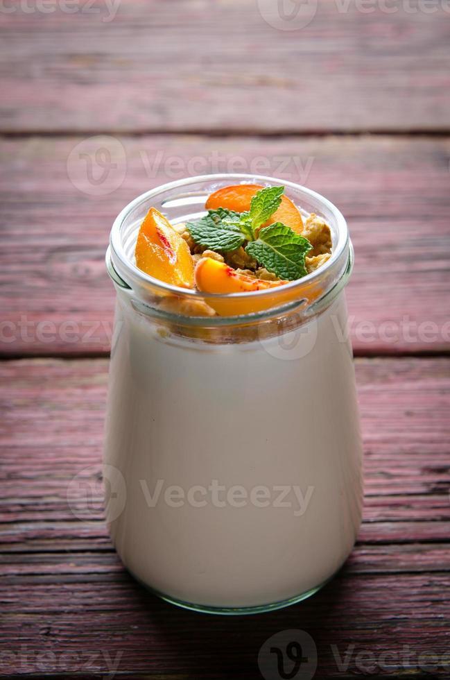dicker griechischer Joghurt mit Müsli, Pfirsichen und Minze foto