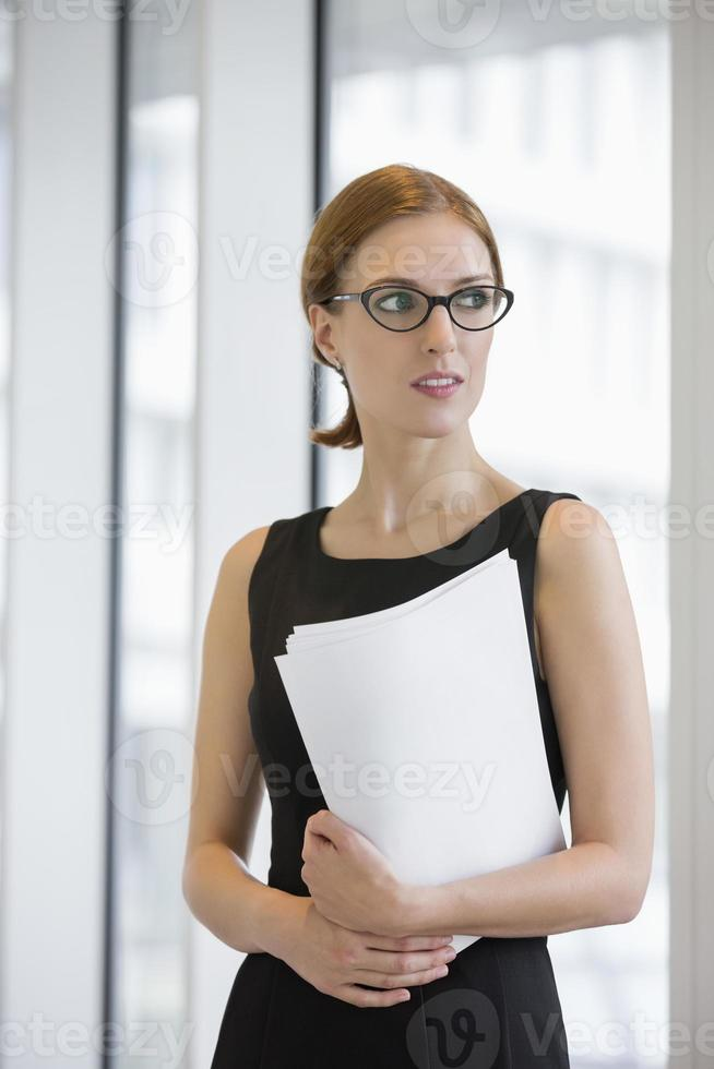 nachdenkliche Geschäftsfrau, die Dokumente im Amt hält foto