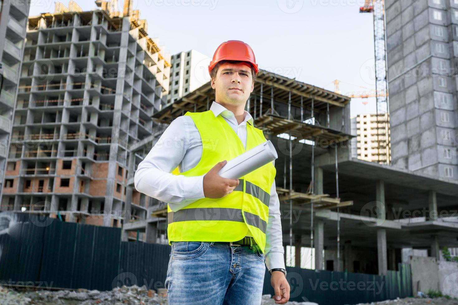 Porträt des Architekten im Helm, der auf Baustelle aufwirft foto
