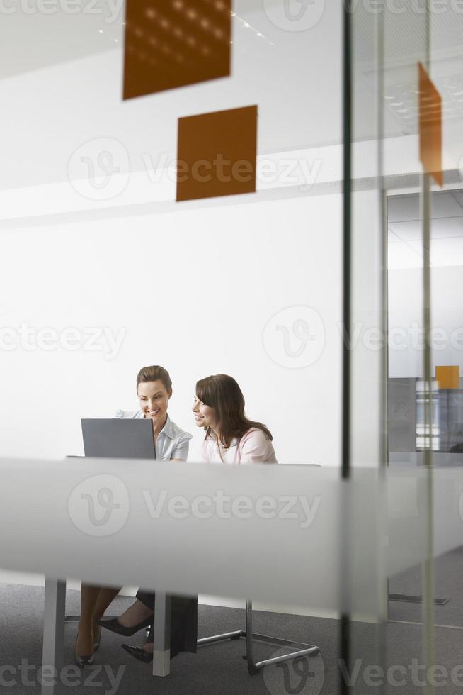 Geschäftsfrauen diskutieren über Laptop im Büro foto