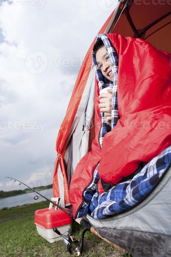 Teenager sitzt im Zelt beim Aufwärmen foto