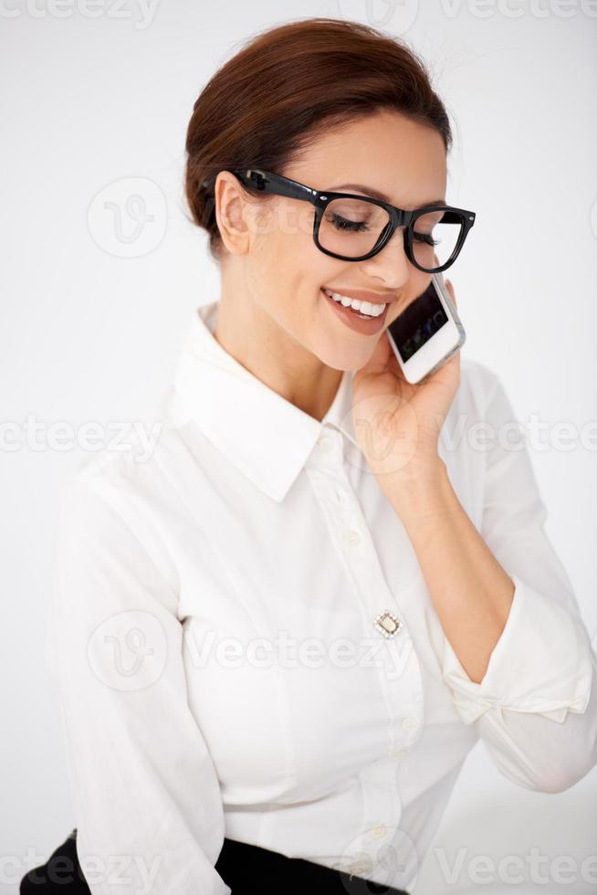 Geschäftsfrau in Brille, die auf einem Handy plaudert foto